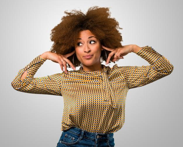 Afro kobieta zakrywająca uszy