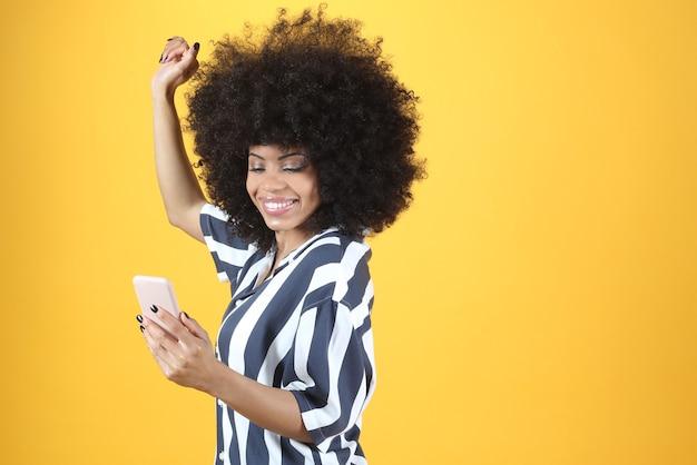 Afro kobieta ze smartfonem tańczącym na żółtym tle