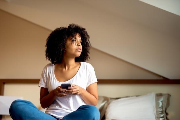 Afro kobiety obsiadanie na łóżkowej mienie wiszącej ozdobie i patrzeć przez okno.