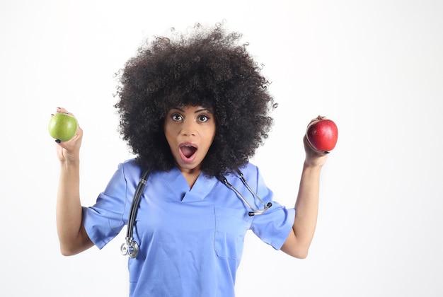 Afro lekarka z jabłkami w ręku na białym tle