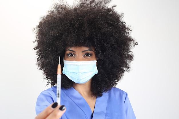 Afro Lekarka Z Maseczką Medyczną Nauczającą Strzykawką, Białe Tło Premium Zdjęcia