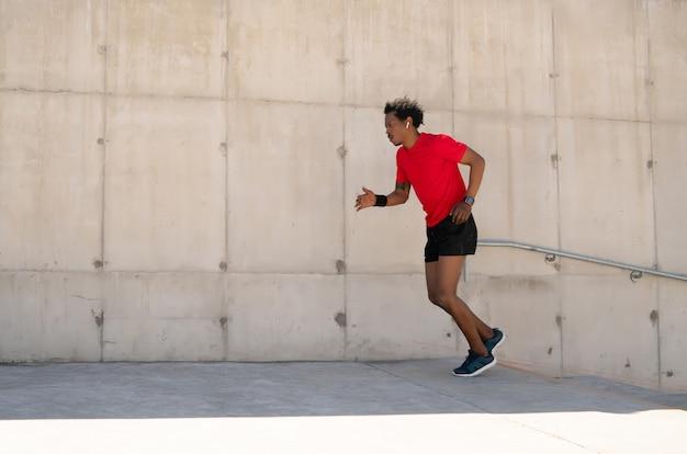 Afro lekkoatletycznego mężczyzna działa i robi ćwiczenia na świeżym powietrzu na ulicy