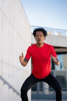Afro lekkoatletycznego mężczyzna robi ćwiczenia na świeżym powietrzu przy schodach