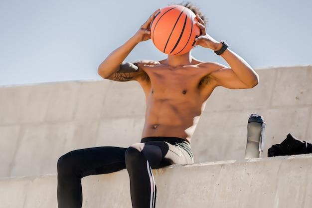Afro lekkoatletycznego mężczyzna trzyma piłkę do koszykówki i relaks po treningu na świeżym powietrzu