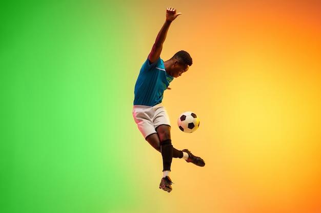 Afro-męska piłka nożna, trening piłkarza w akcji na białym tle na gradientowym tle studio w świetle neonowym. pojęcie ruchu, działania, osiągnięć, zdrowego stylu życia. kultura młodzieżowa.