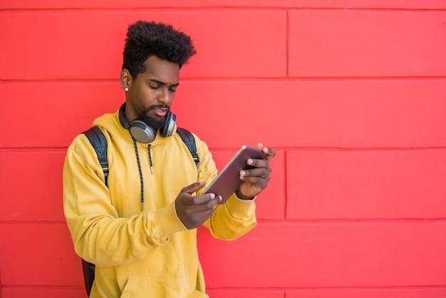 Afro mężczyzna używa jego cyfrową pastylkę z słuchawkami.
