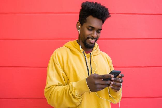 Afro mężczyzna używa jego telefon komórkowego.