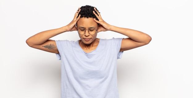Afro młoda czarna kobieta czuje się zestresowana i sfrustrowana, podnosi ręce do głowy, czuje się zmęczona, nieszczęśliwa i ma migrenę