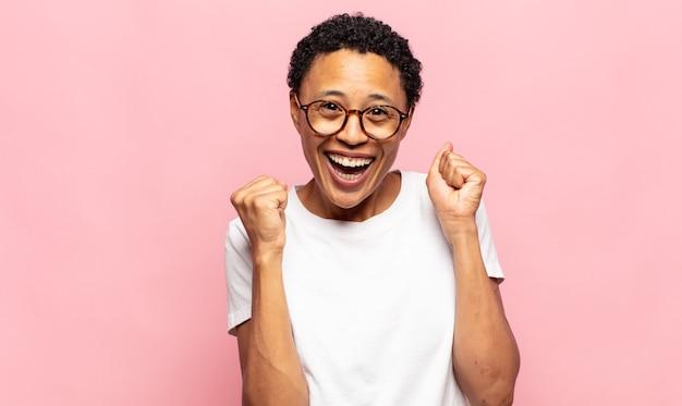 Afro młoda czarna kobieta czuje się zszokowana, podekscytowana i szczęśliwa, śmiejąca się i świętująca sukces, mówiąca wow!