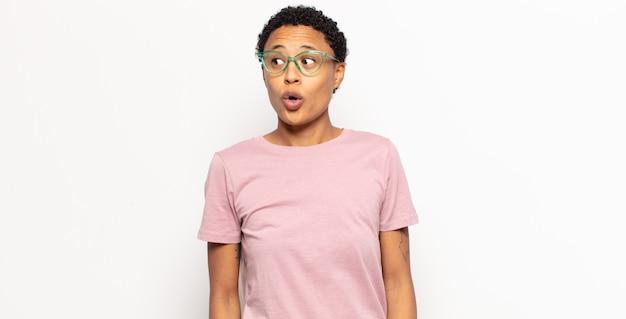 Afro młoda czarna kobieta czuje się zszokowana, szczęśliwa, zdumiona i zaskoczona, patrząc w bok z otwartymi ustami