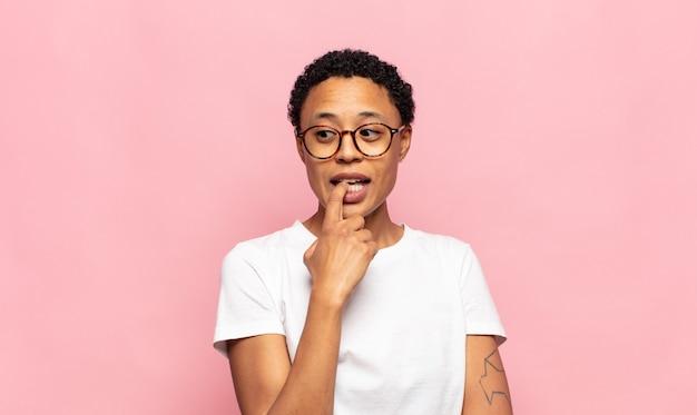 Afro młoda czarna kobieta o zdziwieniu, zdenerwowaniu, zmartwieniu lub przestraszeniu, spoglądająca w bok w kierunku miejsca na kopię