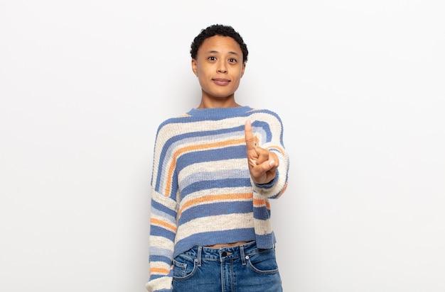 Afro młoda czarna kobieta uśmiecha się dumnie i pewnie, triumfalnie tworząc pozę numer jeden
