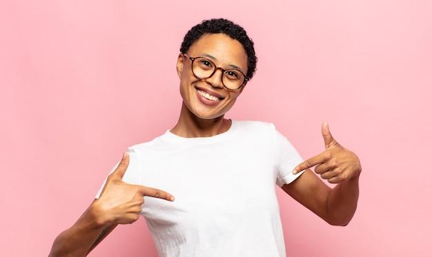Afro młoda czarna kobieta wyglądająca na dumną, arogancką, szczęśliwą, zaskoczoną i usatysfakcjonowaną, wskazującą na siebie, czującą się jak zwycięzca
