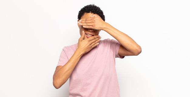 """Afro młoda czarna kobieta zakrywająca twarz obiema rękami mówiąca """"nie"""" do kamery! odmawianie zdjęć"""