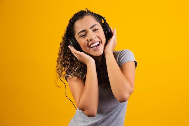 Afro młoda dziewczyna ze słuchawkami słucha muzyki