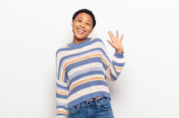 Afro młoda kobieta uśmiecha się radośnie i wesoło, macha ręką, wita i wita lub żegna się