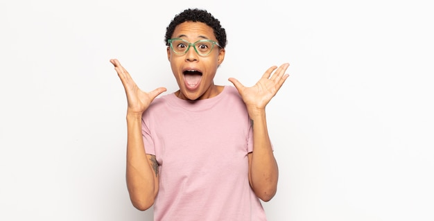 Afro młoda murzynka czuje się zszokowana i podekscytowana, śmiejąca się, zdumiona i szczęśliwa z powodu niespodziewanej niespodzianki
