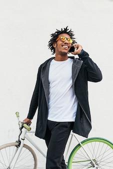 Afro młody człowiek za pomocą telefonu komórkowego i roweru stacjonarnego na ulicy.