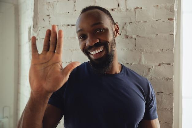 Afro-muzyk na tle białego ceglanego muru, wesoły i szczęśliwy. odpoczywając po koncercie online, pokazując miły gest, uśmiechając się