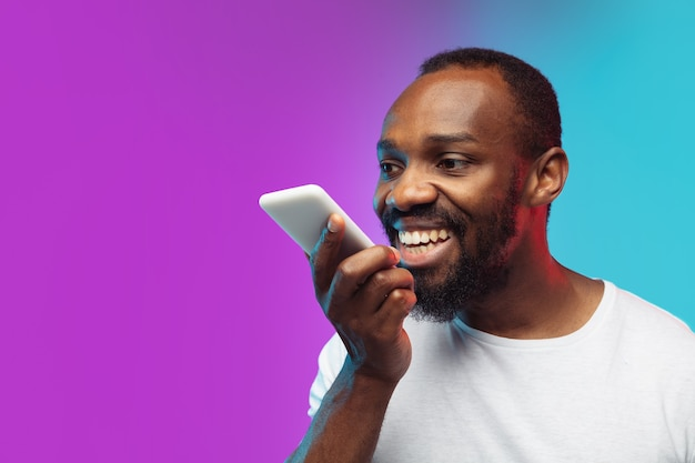 Afro-portret młodego mężczyzny na tle studio gradientu w neon. piękny męski model w stylu casual, biała koszula. pojęcie ludzkich emocji, wyraz twarzy, sprzedaż, reklama.