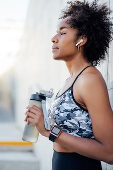 Afro sportowe kobieta wody pitnej i relaks po treningu na świeżym powietrzu. pojęcie sportu i zdrowego stylu życia.