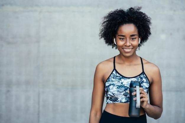Afro sportowe kobieta wody pitnej i relaks po treningu na świeżym powietrzu. sport i zdrowy tryb życia.