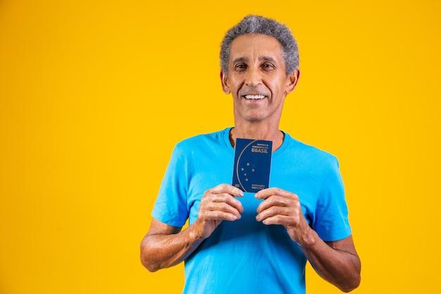 Afro starszy mężczyzna trzyma w rękach brazylijski paszport.