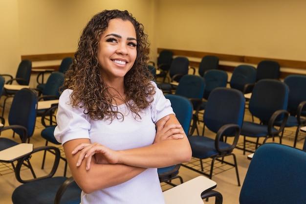 Afro student w klasie z rękami skrzyżowanymi patrząc na kamery uśmiecha się. młody student z klasą w tle.