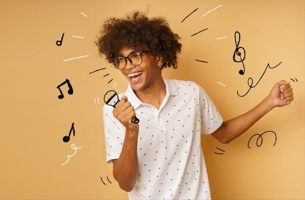 Afro szczęśliwy człowiek z mikrofonem śpiewa piosenkę