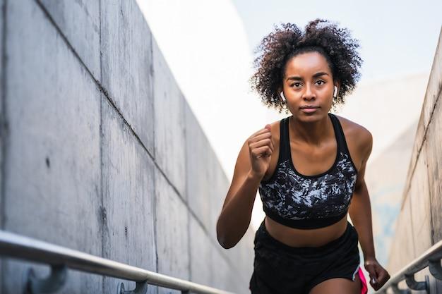 Afro wysportowana kobieta biegająca i wykonująca ćwiczenia na świeżym powietrzu