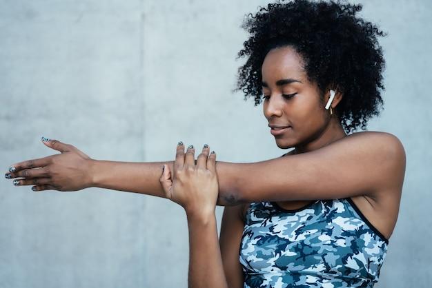 Afro wysportowana kobieta, rozciągająca ramiona i rozgrzewająca się przed ćwiczeniami na świeżym powietrzu.