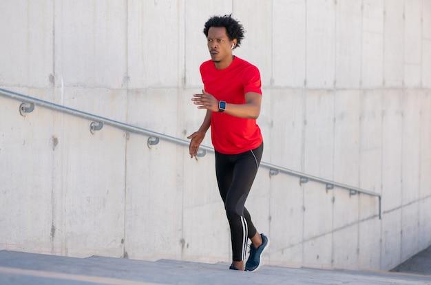 Afro wysportowany mężczyzna robi ćwiczenia i bieganie po schodach na zewnątrz. pojęcie sportu i zdrowego stylu życia.