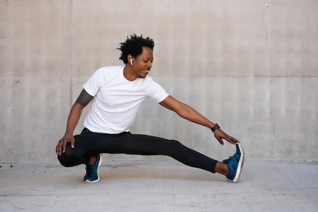 Afro wysportowany mężczyzna rozciągający nogi i rozgrzewający się przed ćwiczeniami na świeżym powietrzu. pojęcie sportu i zdrowego stylu życia.