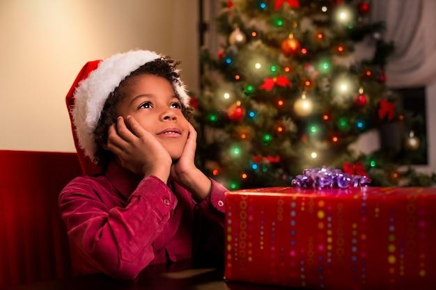 Afroamerican chłopiec w pobliżu prezentu świątecznego.
