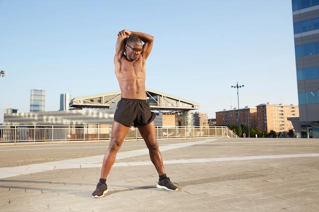Afroamerican człowiek robi rozciąganie w środowisku miejskim
