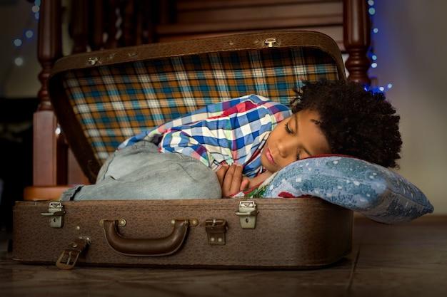 Afroamerican dziecko śpi w walizce. drzemka chłopca w walizce. potrzebuje odpoczynku. wakacje go męczą.
