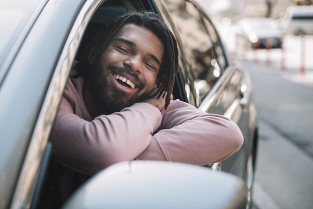 Afroamerican mężczyzna pozuje w samochodzie