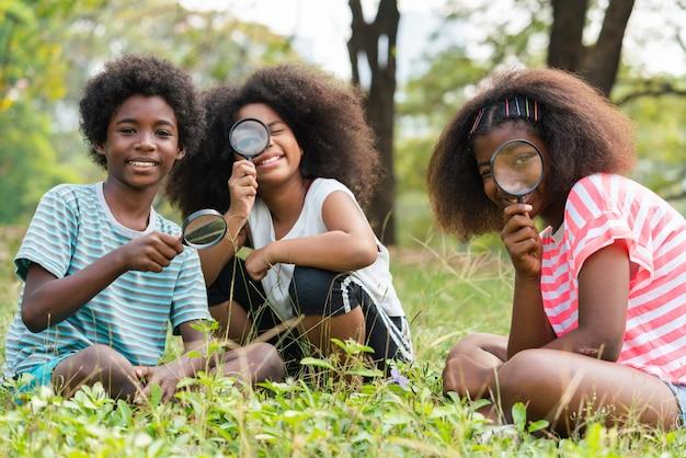Afroamerykanie dzieci siedzą na trawie i patrzą przez szkło powiększające pomiędzy uczą się poza klasą. koncepcja edukacji zewnętrznej.