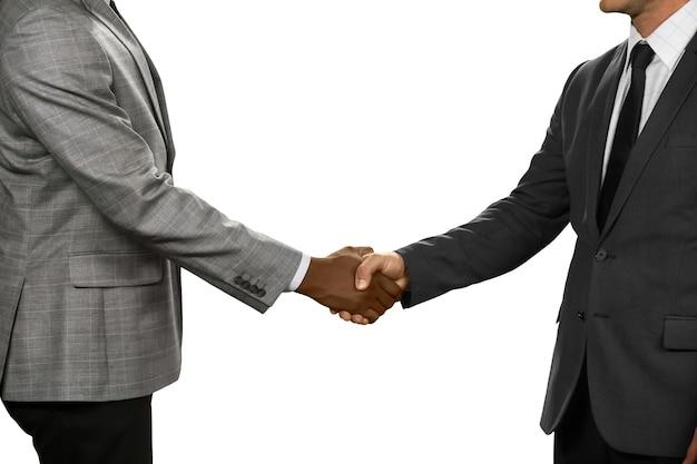 Afroamerykanie i europejczycy podają sobie ręce. unia interesów. moje gratulacje. spacyfikowany przez zasady etykiety.