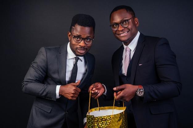 Afroamerykanie męscy partnerzy biznesowi trzymający torby na zakupy na czarnym tle w studio. czarny piątek wyprzedaż sezonowa koncepcja