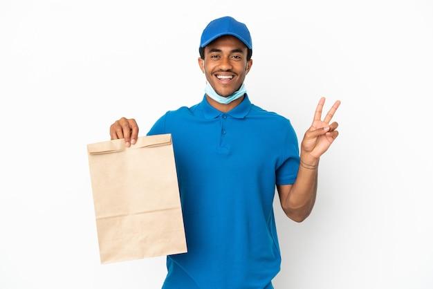 Afroamerykanin biorący torbę jedzenia na wynos na białym tle uśmiechający się i pokazujący znak zwycięstwa
