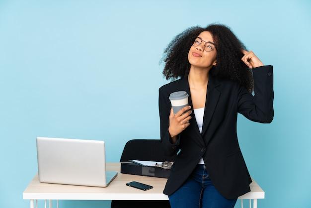 Afroamerykanin biznes kobieta pracuje w swoim miejscu pracy, mając wątpliwości i myślenia