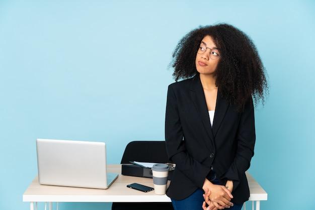 Afroamerykanin biznes kobieta pracuje w swoim miejscu pracy, robiąc gest wątpliwości patrząc z boku