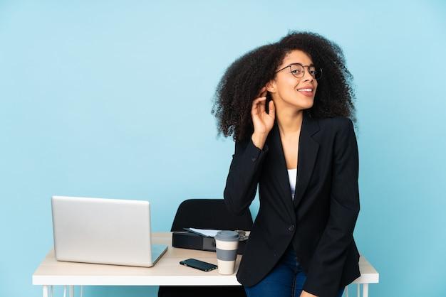 Afroamerykanin biznes kobieta pracuje w swoim miejscu pracy, słuchając czegoś, kładąc rękę na uchu