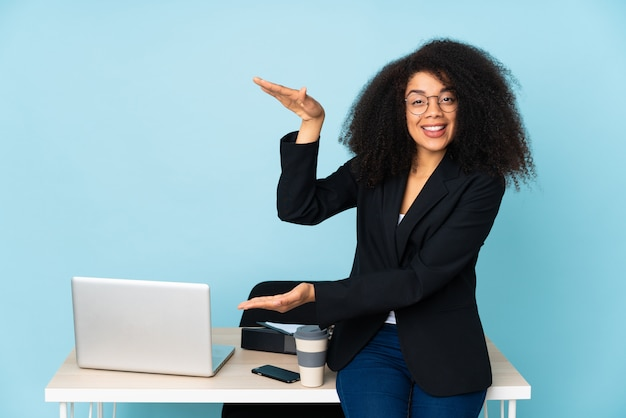 Afroamerykanin biznes kobieta pracuje w swoim miejscu pracy, trzymając copyspace, aby wstawić reklamę