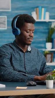 Afroamerykanin czarny menedżer za pomocą słuchawek do słuchania muzyki podczas pracy w domowym biurze na ko...