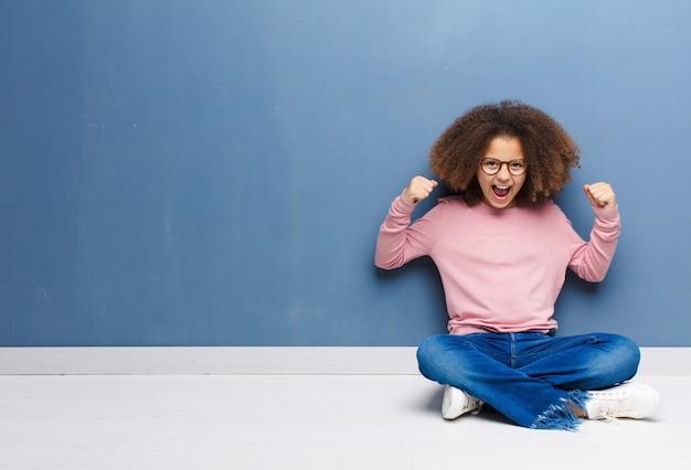 Afroamerykanin dziewczynka czuje się szczęśliwy, zaskoczony i dumny, krzyczy i świętuje sukces z wielkim uśmiechem na podłodze