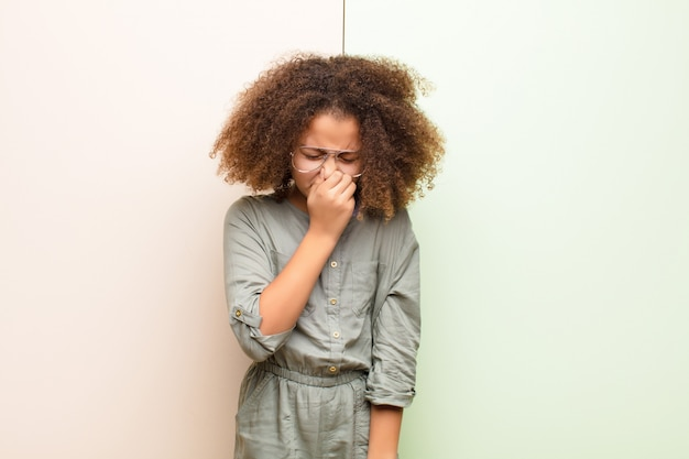 Afroamerykanin dziewczynka czuje się zdegustowany, trzymając nos, aby uniknąć wąchania nieprzyjemnego i nieprzyjemnego smrodu na płaskiej ścianie