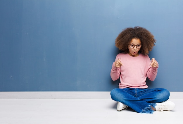 Afroamerykanin dziewczynka czuje się zszokowana, z otwartymi ustami i zdziwiona, patrząc i wskazując w dół z niedowierzaniem i zaskoczeniem, siedząc na podłodze