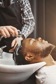 Afroamerykanin. facet siedzi na krześle. myć włosy.